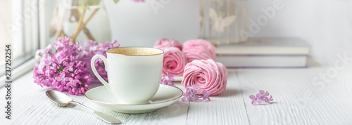 Fototapeta Bouquet of lilacs, cup of coffee, homemade marshmallow and books. Romantic spring morning. Selective focus obraz
