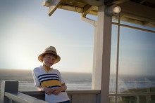 Portrait Of A Young Boy Standing On A Balcony Overlooking The Sea On A Sunny Day.