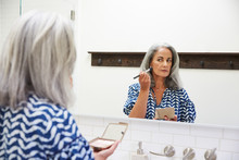 Senior Woman With Grey Hair Putting On Makeup In Bathroom Mirror