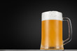 Glass of beer with foam on a dark background