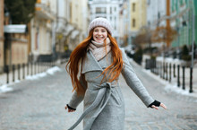 Gorgeous Smiling Redhead Girl Wearing Stylish Winter Outfit Walking In City, Spinning Around. Empty Space