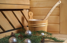 Spa, Sauna And Wellness Setting With Water Bucket, Oil Essence, Cones, Christmas Tree Branches, White Towel On Wooden Background. Autumn Winter Wellness Concept Relax And Treatment Therapy. Close Up
