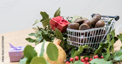 Fall and winter seasonal background, copy space image with laurel leaves and a shopping trolley full of chestnuts