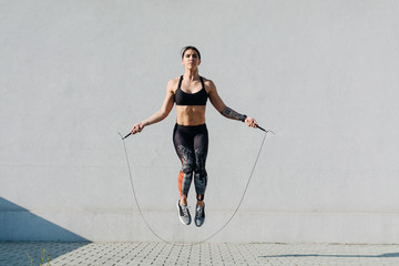 Young woman skipping ropes ...