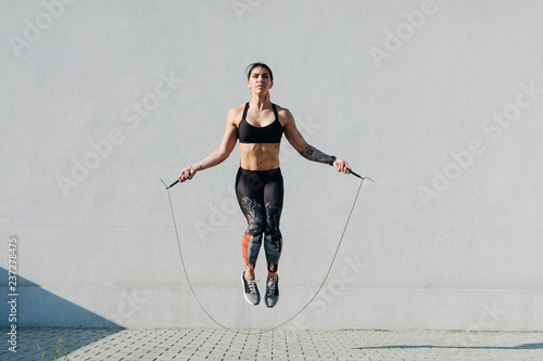 Fotografiet  Young woman skipping ropes outdoors