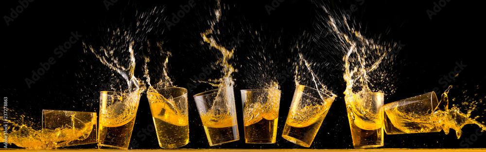 Fototapeta Eight golden tequila shots splashing