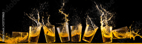 Photo Eight golden tequila shots splashing