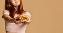 Close Up Portrait Of A Hungry Young Woman Eating Burger Isolated Over Nude Background