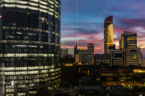 Poster London Abu Dhabi city beautiful winter clouds and towers at sunset with green show light celebration