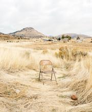 Single Chair Empty In Dry Grass Desert Field Environment.