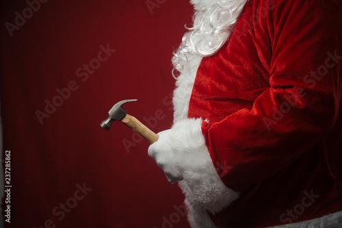 Santa Claus holding hammer in hands busy preparing decoration Wallpaper Mural