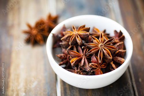 Star anise in a bowl on wooden table, herbs and spices, food ingredients Wallpaper Mural