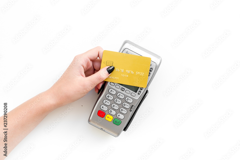 Fototapeta Pay by payment terminal. Paypass  technology. Woman's hand hold credit card, bring card to terminal  on white background top view copy space
