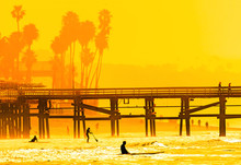 Surfers At San Clemente Pier In The Golden Light Of A Summer Sunset In Southern California
