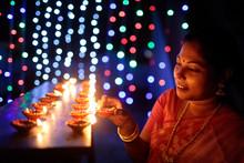 Woman Lighting Earthen Oil Lam...