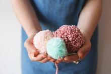 Close Up Of Hands Holding Home Made Pom Poms