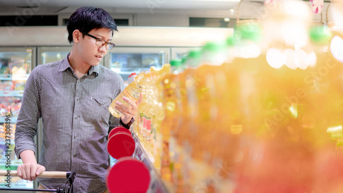 Fotobehang Aromatische Young Asian man with eyeglasses choosing vegetable oil from product shelf in supermarket. shopping lifestyle in grocery store concept