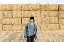 Lifestyle Portrait Of Young Adult Female Wearing Denim Coat In Hay Field After Harvest