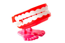 Stand Up Comedy Show, Windup Joke Toy And Prank Toys Concept With A Pair Of Red Wind Up Chattering Teeth With Pink Legs Isolated On White Background With A Clip Path Cutout