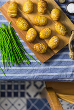 Baked Hasselback Potatoes On A Wooden Board