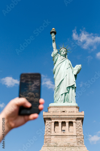 Poster Historisch mon. tourist taking picture on mobile phone of Statue of Liberty