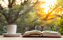 A Cup Of Coffee And Glasses On Book On The Wooden Table With Morning Light And Blurred Nature Background