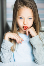 Cheeky Cute Blond Little Girl Playing With Dried Fruit