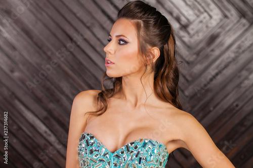 Fotografía  Brunette young woman in sexy blue dress, studio wall indoor