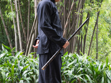 One Chinese Man Playing Vertical Bamboo Flute In The Bamboo Wood