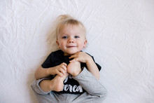 Happy, Smiling Toddler Holds His Feet