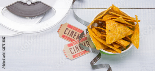 a bucket of nachos on a light background, two movie tickets and film stock