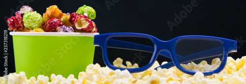 blue 3 d glasses on a black background surrounded by popcorn