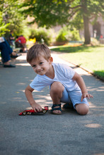 Cute Little Boy Playing With A Car Toy In A Park In Paris In Summer