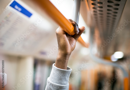 Man holding on to a handrail on a train
