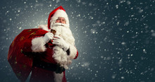 Santa Claus Holding A Bag With Presents And Ringing A Bell On A Dark Background With Snow