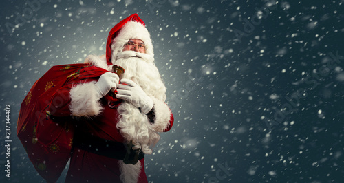Photo  Santa Claus holding a bag with presents and ringing a bell on a dark background