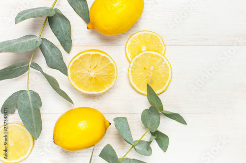 Whole and sliced fresh lemon, eucalyptus leaves on white wooden background. Flat lay, top view, copy space. Minimal fruit concept design. Yellow citrus, lemons