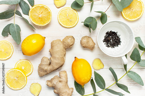 Fresh ginger root, cup tea with brewing inside, lemon, eucalyptus leaves on white wooden background. Flat lay, top view, copy space. Minimalistic style, seasoning, spice, ingredient for tea.