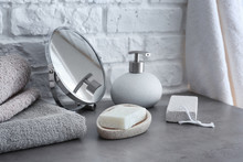 Soap With Towels And Mirror On Grey Table In Bathroom