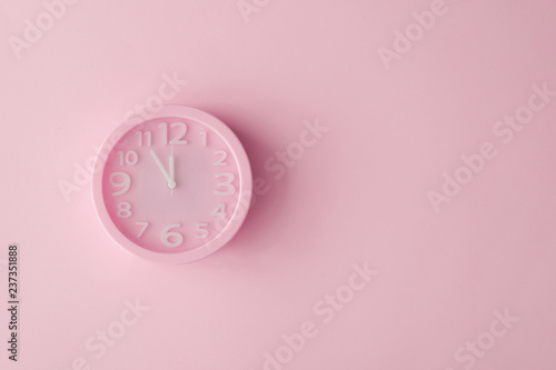 Obraz Pastel pink clock on pink painted wall. Minimal time concept. Chrismas eve or new year idea. - fototapety do salonu