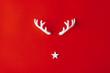 Leinwanddruck Bild - Reindeer antlers with star on red background. Christmas minimal Greeting card.