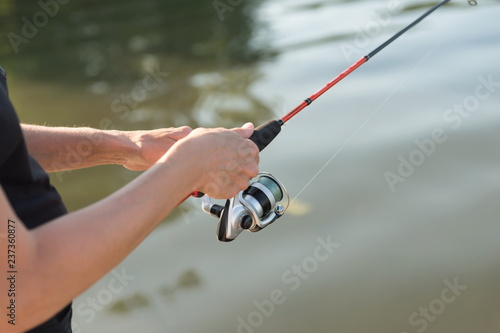 Fotografía  Fisherman's hands are fishing on a spinning in the water on a sunny summer day