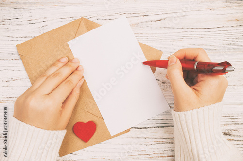 Obraz na plátně Hand of girl writing love letter on Valentine Day