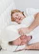 The elderly man covered his ears with a pillow so as not to hear the snoring of his wife. Focesed on woman