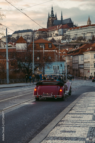 Türaufkleber London roten bus Prague, Czech Republic - Winter, 2018: A red tram and people on a bridge with Prague Castle in the background