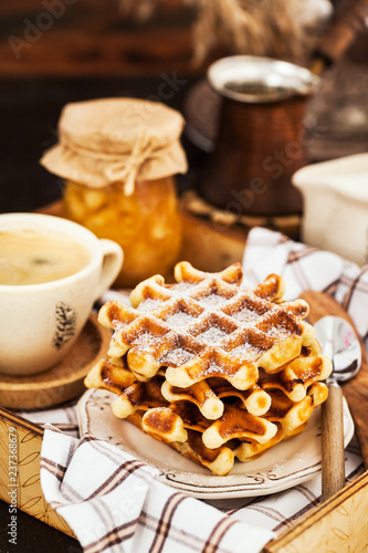 Fotografía  Breakfast with belgian waffles, jam and coffee on tray, rustic background