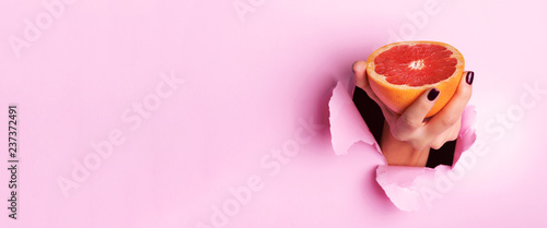 Female hand holding half of grapefruit through torn pink paper background. Fresh orange juice. Vegan, vegetarian concept. Banner with copy space