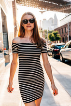 USA, New York, Brooklyn, Dumbo, Portrait Of Smiling Woman Wearing Striped Dress And Sunglasses