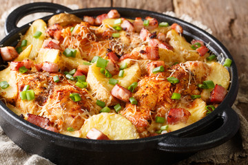 Delicious ranch casserole of chicken fillet with potatoes, bacon and cheese close-up in a pan. horizontal