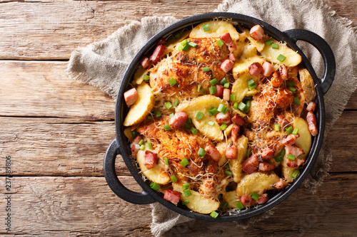 Photo Stands Ready meals spicy chicken breast with potatoes, bacon and cheese close-up in a frying pan. Horizontal top view